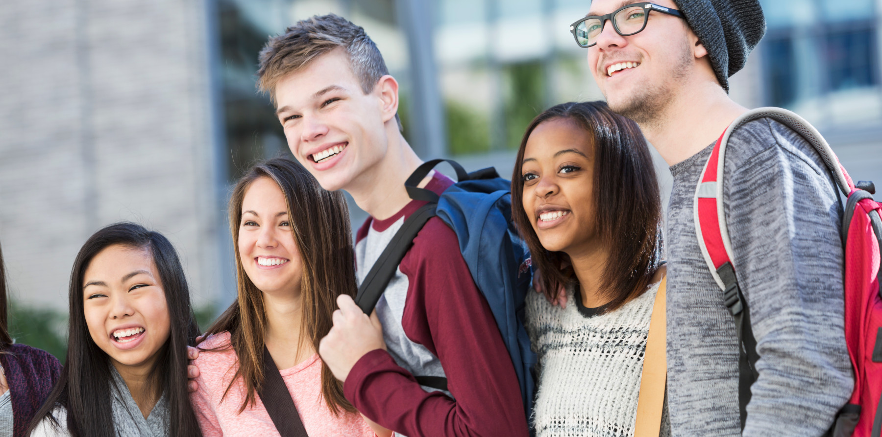A multi-ethnic group of high school or college students standing in front of a school building. They are lined up in a row, carrying bookbags.