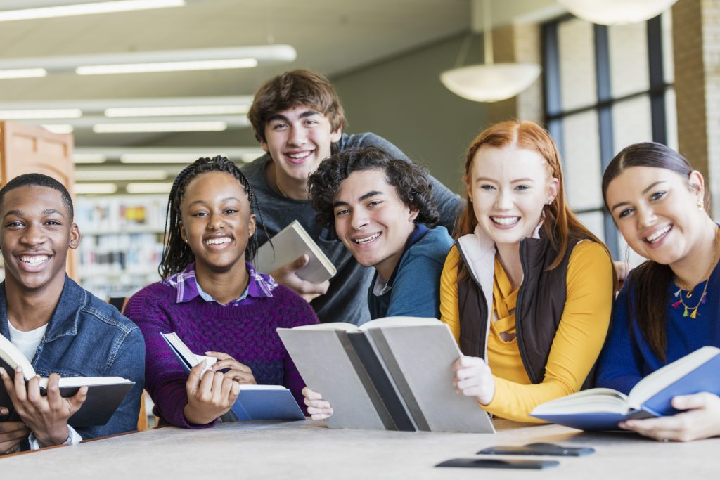 A multi-ethnic group of six high school students, 15 to 17 years old, studying together in the library. They are sitting at a table smiling at the camera.