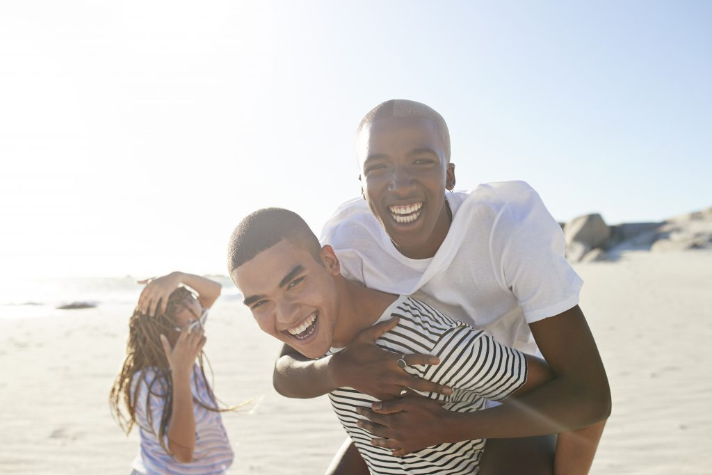 Excited man piggybacking friend with woman in background at beach