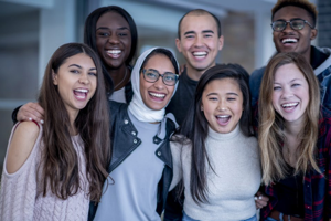 A multi-ethnic group of University students posing for a portrait, smiling and having fun.