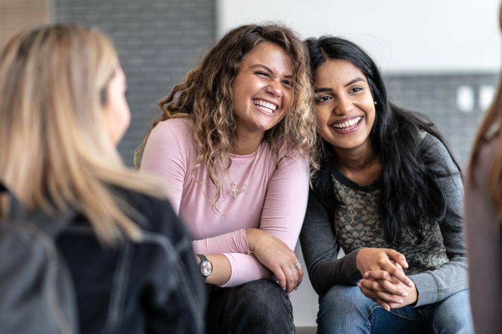 Two female young adults sit closely together, with their heads resting against each others, during a group therapy session.  One is of African decent and the other is of Indian decent.  Bother are dressed casually and are sitting among their multi-ethnic peers with smiles on their faces.