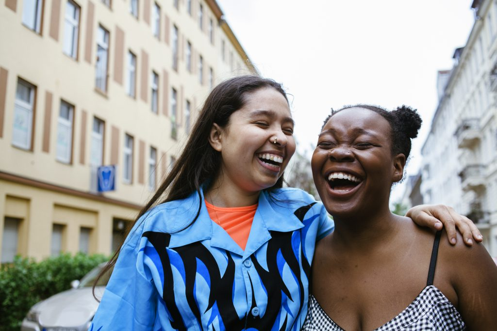 Laughing lesbian couple background is city buildings. Part of the LGBTQ Portrait series.